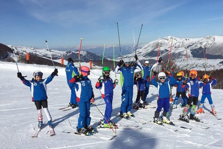 Group of happy kids on a ski slope with their ski poles in the air